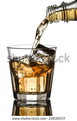 Whiskey being poured into a glass on white background - stock photo