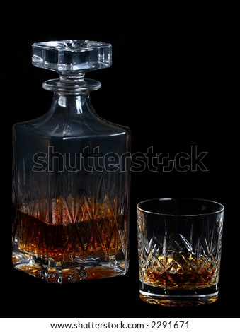 Whiskey bottle and whiskey (tumbler) glass on a black background