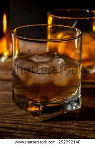 Whiskey, bourbon or brown rum with ice on wood table