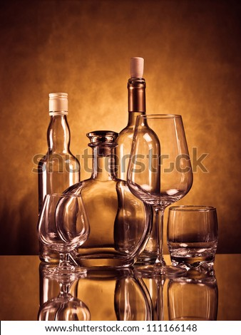 Whiskey, cognac and wine bottles with glasses on brown grunge background