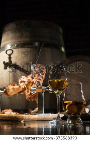 whiskey, cognac, calvados with boiled pork knuckle on the background of oak barrels - stock photo