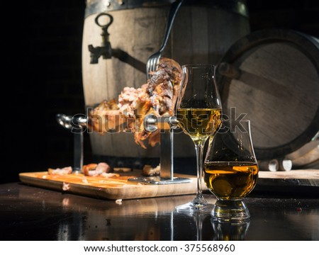 whiskey, cognac, calvados with roasted pork knuckle on the background of oak barrels - stock photo