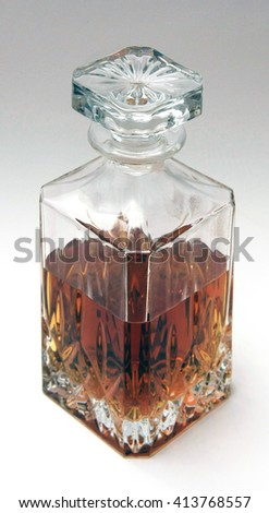 Whiskey Decanter half full with spirit on white background