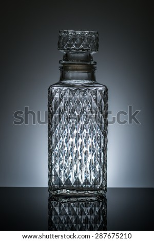 whiskey decanter with dark blue background - stock photo