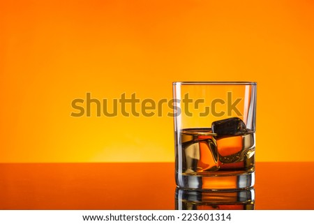 Whiskey drink reflected on glass with orange background - stock photo