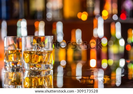 Whiskey drinks on bar counter with blur bottles on background - stock photo