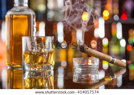 Whiskey drinks on bar counter with blur bottles on background. - stock photo