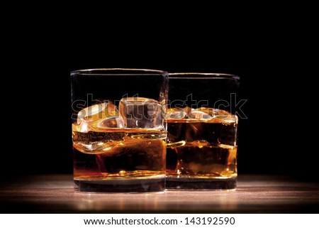 Whiskey drinks on wooden table - stock photo