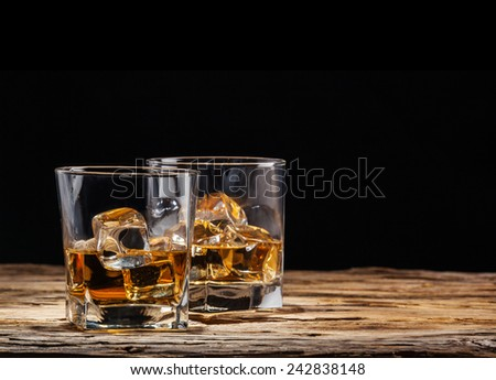 Whiskey drinks on wooden table with black background - stock photo