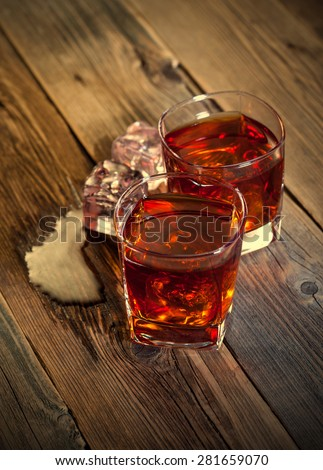 Whiskey drinks with ice on wooden table. retro style - stock photo