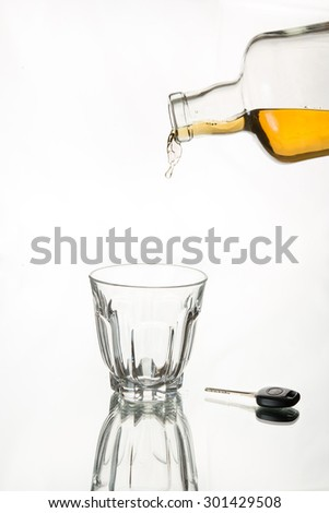 Whiskey freezes in the air after coming out of bottle, with car key in frame,Isolated, white background. Drink responsibly; Drink aware; Don't drink and drive.  - stock photo