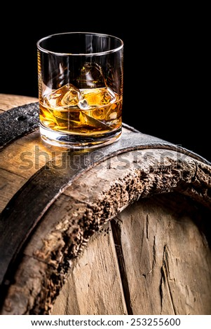 Whiskey glass and old wooden barrel - stock photo