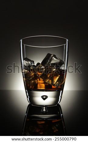 Whiskey glass on grey background - stock photo