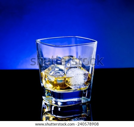 whiskey glass on light tint blue disco on black table with reflection - stock photo
