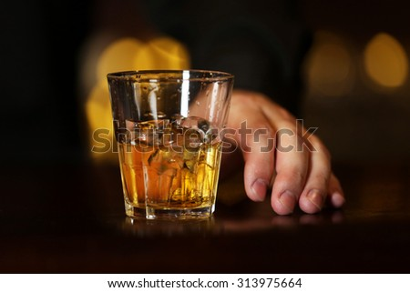 Whiskey glass tumbler in male hand on bar counter  - stock photo