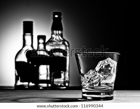 Whiskey glass with bottles in the background - stock photo
