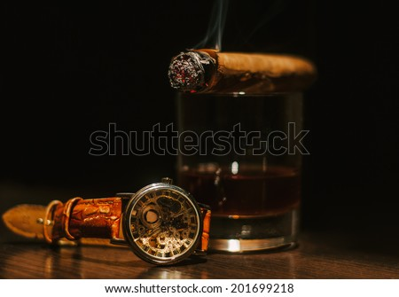 Whiskey glass with cigar and watch - stock photo