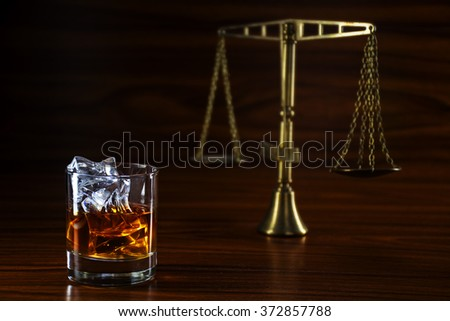 whiskey glass with ice and the scales of justice blurred in the background on a wooden table, concept alcohol and conflicts with the law - stock photo