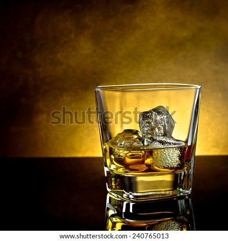 whiskey glass with ice and warm light on black table with reflection and warm atmosphere