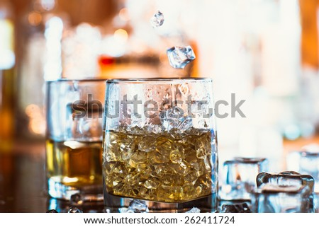 whiskey glass with ice and  warm light on black table with reflection, warm atmosphere - stock photo
