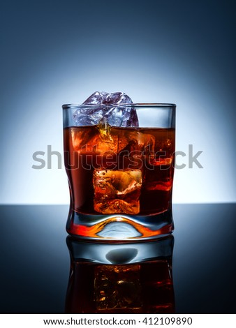 Whiskey glass with ice cubes on black glass surface over blue background. - stock photo