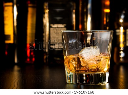 whiskey glass with ice in front of bottles on wood table - stock photo