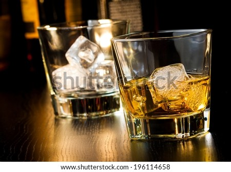 whiskey glass with ice in front of empty whiskey glass on wood table - stock photo