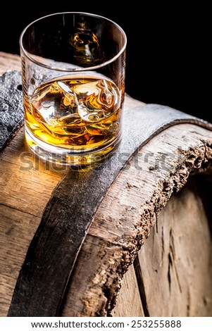 Whiskey glass with ice on old oak barrel - stock photo