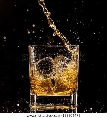 Whiskey glass with splash, isolated on black background - stock photo