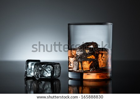 Whiskey glass with two ice cubes on a black surface