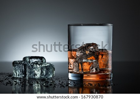 Whiskey glass with wet ice cubes on black surface - stock photo