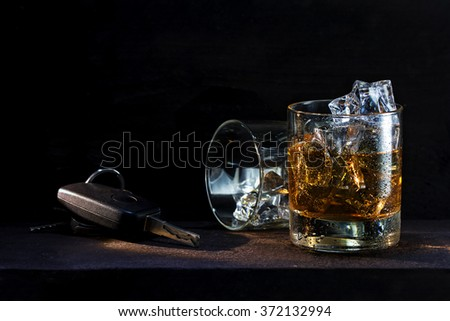 whiskey glasses with ice and car keys on a rustic wooden table, copy space in the dark background, concept against drinking alcohol and driving - stock photo