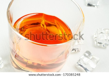 Whiskey in a glass on a white background. Ice nearby.