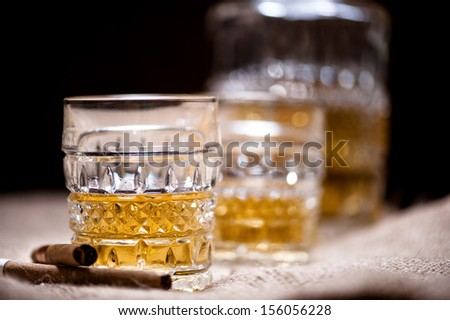 Whiskey in a glass on the rocks with bottle and vintage background - stock photo
