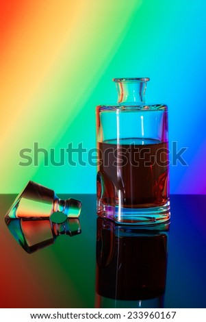 whiskey in a glass transparent bottle on the background of the rainbow