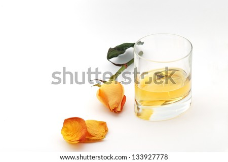 whiskey in a glass with an orange rose on a white background from above
