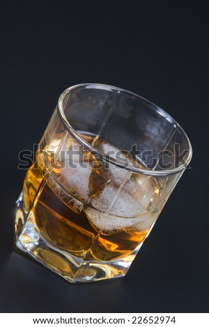 Whiskey in a glass with ice against a dark background