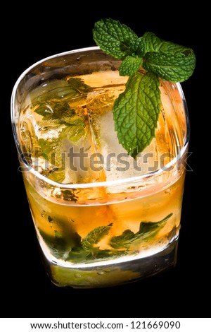 whiskey in a glass with ice and fresh mint backlit and isolated on a black background - stock photo