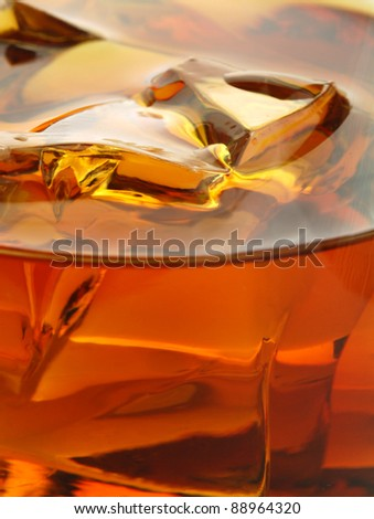 Whiskey in glass with ice. Macro shot. - stock photo
