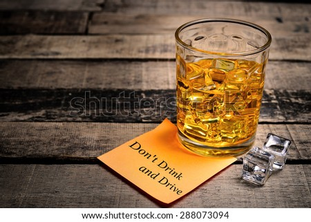Whiskey in light pool and Don't Drink and Drive note on brown table - stock photo