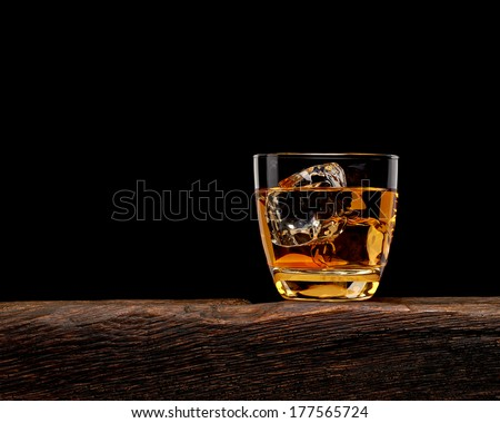 Whiskey in rocks glass with ice cubes on log table - stock photo