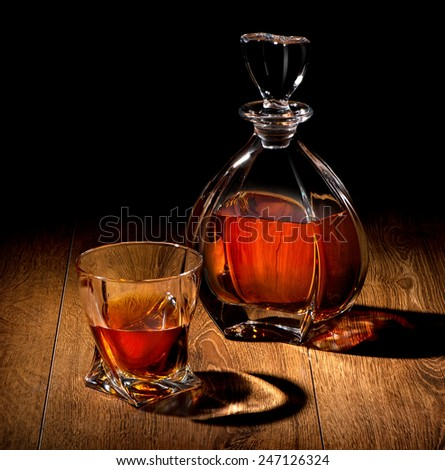 Whiskey on a wooden table on black background - stock photo