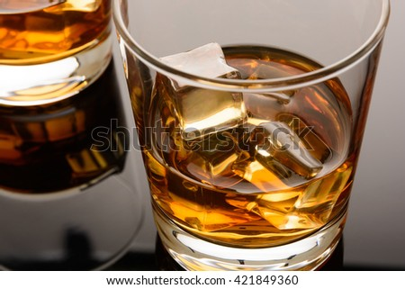 Whiskey on the rocks in the glass. Macro. Whisky with ice - stock photo