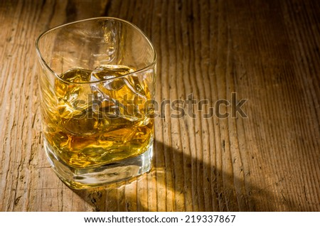 Whiskey on the rocks on a wooden background