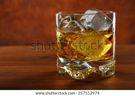 Whiskey on the rocks on wooden table , red background - stock photo