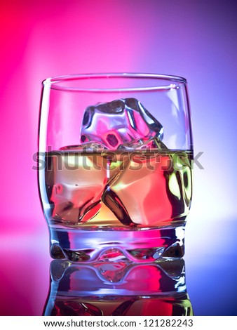 Whiskey on the rocks over vibrant background