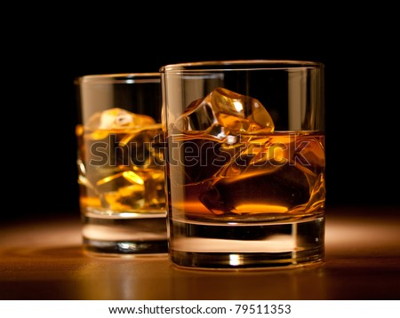 whiskey on the rocks, vibrant colors on black - stock photo