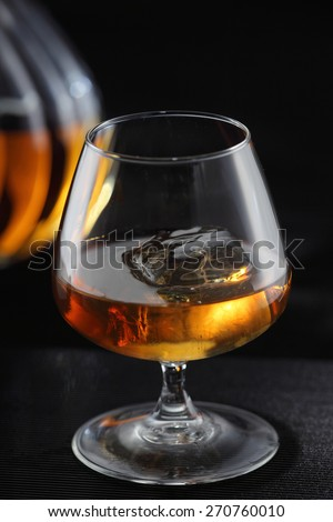 Whiskey on the rocks, whiskey glass, whiskey bottle - stock photo