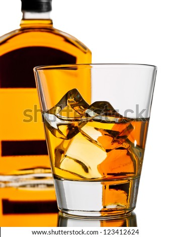 Whiskey on the rocks with a bottle on the background - stock photo