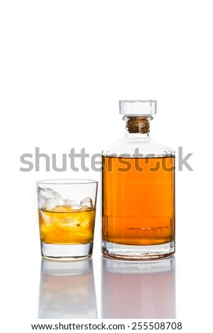 Whiskey on the rocks, with a whiskey bottle isolated in white - stock photo